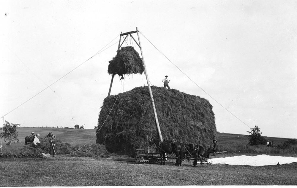 Using poles, a sling and a winch to stack hay. Cornfalfa Farms collection, New Berlin Historical Society.