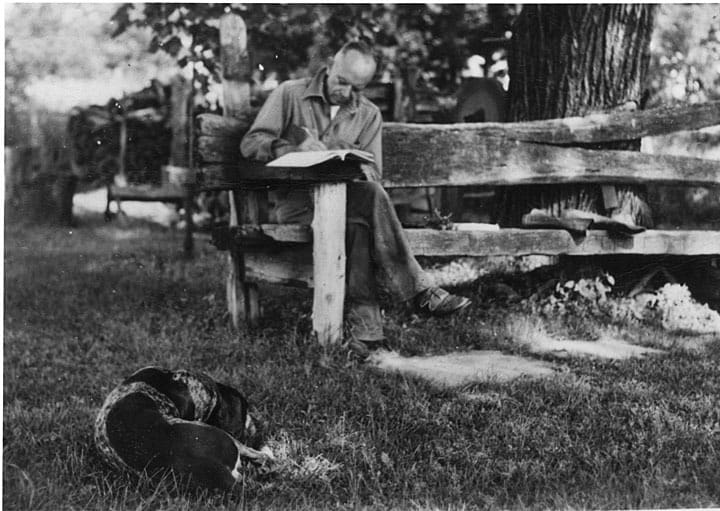 Aldo Leopold writing at his shack near Baraboo, Wisconsin with dog Flick, 1930-1939. Aldo Leopold Foundation and UW-Madison Archives.