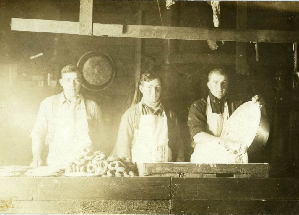 Three men (and a large pile of donuts) in the mess hall of an unidentified northwoods Wisconsin logging camp. Langlade County Historical Society.