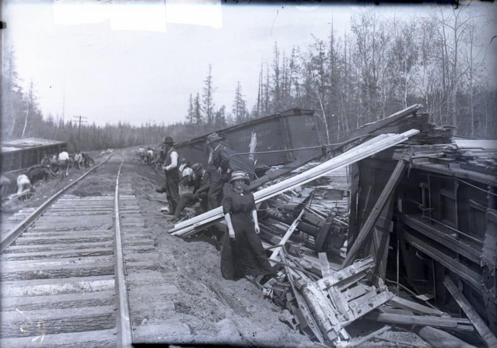 Overturned rail cars with passengers standing nearby. Glass negative by A. J. Kingsbury, 1900-1920. Langlade County Historical Society.