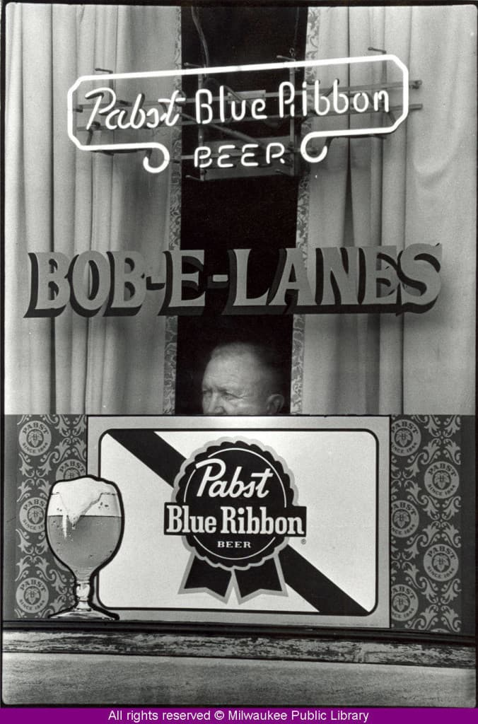 A man peers out a window at Milwaukee's Bob-E-Lanes bowling alley and tavern.