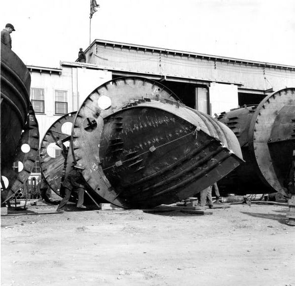 Kewaunee Shipbuilding and Engineering built tugboats as well as large cargo vessels. This image shows rings built around ship hulls in order to roll them upright after welding. According to local history, the rings were necessary because the company only had one crane available due to wartime shortages. Kewaunee Public Library.