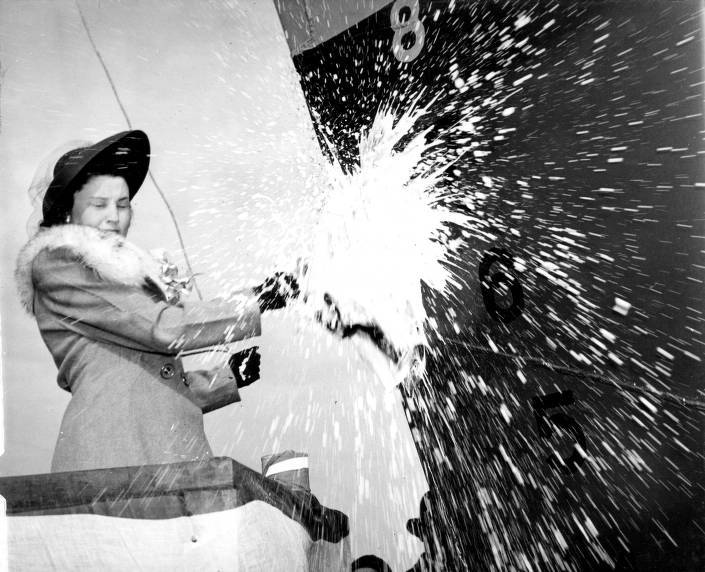 Florence Ratajczak smashes a bottle of champagne to christen a new ship, 1941-1946. Kewaunee Public Library.