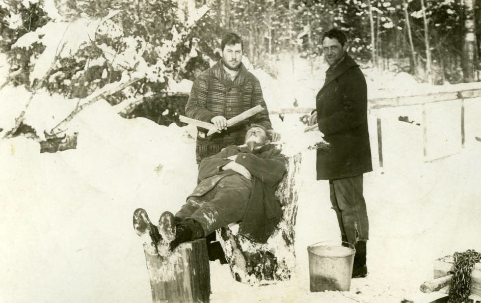 Loggers clown for the photographer as one shaves another. Langlade County Historical Society.
