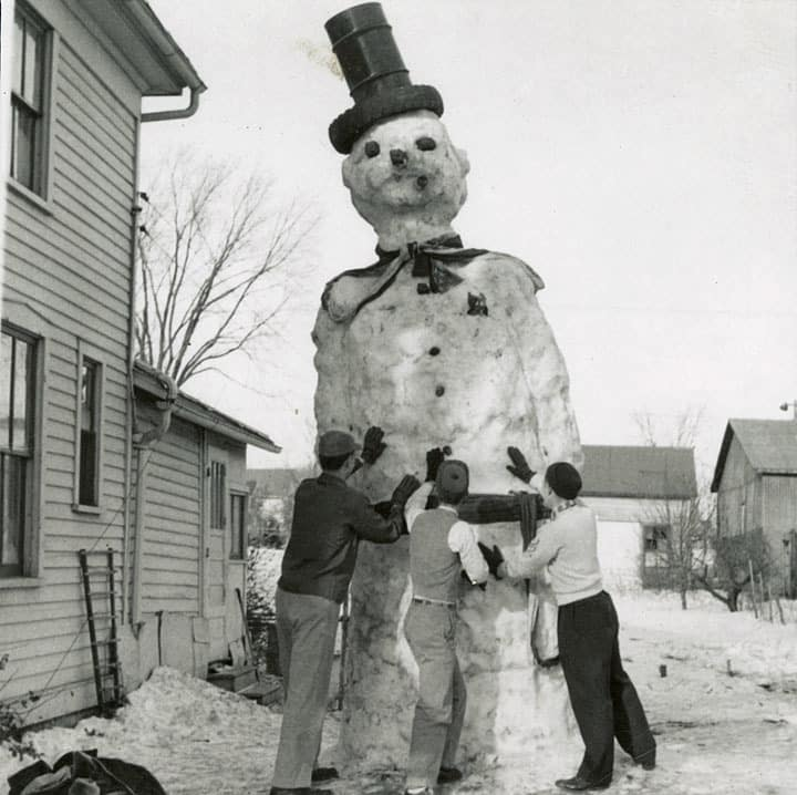 Three young men put the finishing touches on a huge snowman, Kiel, Manitowoc County. Big Streets in a Little City: Kiel, Wisconsin, 1860-1980, Heritage Collection, Kiel Public Library by way of University of Wisconsin Digital Collections