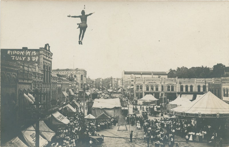 In this postcard, a daring acrobat dangles high above Ripon's central square. Based on the date (July 3), the tents, and the large crowd gathered below, this performance was most likely part of an Independence Day carnival in Ripon. Ripon Historical Society.