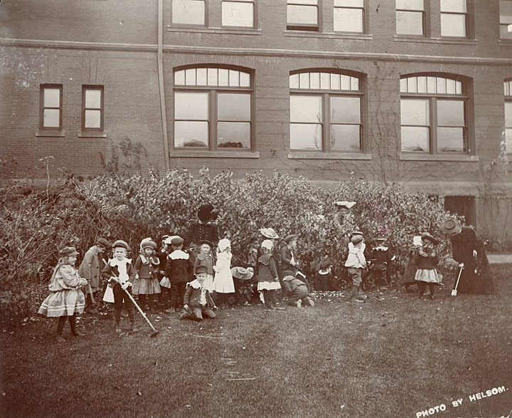 A kindergarten class and three teachers tend a garden outside Bowman Hall on the Stout campus, ca. 1900. University of Wisconsin-Stout.