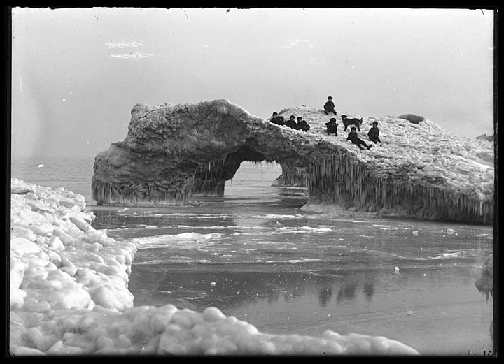 Several boys and a dog play on a massive ice formation on the shore of Lake Michigan, Kenosha County, February 1906. Photo by Louis Milton Theirs. Kenosha History Center.