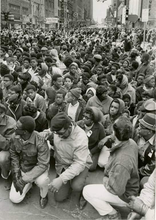 A large crowd kneels in prayer on Wisconsin Avenue in Milwaukee on the first anniversary of the assassination of Dr. Martin Luther King, Jr., May 5, 1969. Photo from the Milwaukee Journal. Milwaukee Public Library.
