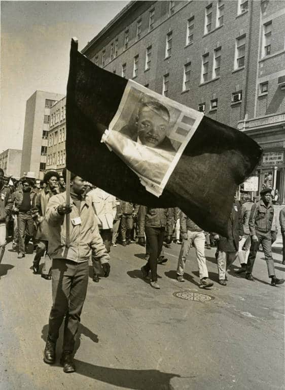 Man waves a flag with Dr. Martin Luther King, Jr.'s portrait on the first anniversary of King's death, Milwaukee, 1969. Milwaukee Public Library.