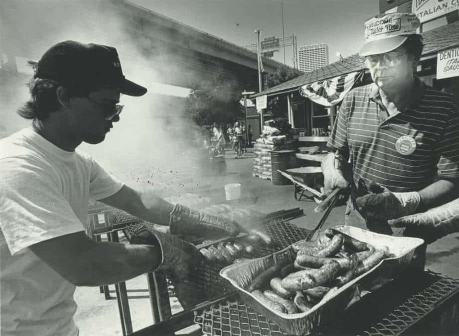 Two men cooking Italian sausages at Milwaukee's Festa Italiana, 1984. Photo by Michael Sears. Milwaukee Public Library.