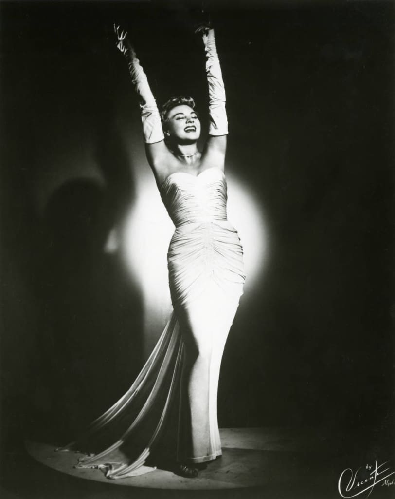 On February 1, 1906, cabaret singer Hildegarde Loretta Sell was born in Adell, Wisconsin. This publicity photo from the late 1950s shows Hildegarde in her trademark long white gloves; her arms are raised in her signature pose. In the Spotlight, Department of Special Collections and University Archives, Marquette University Libraries.