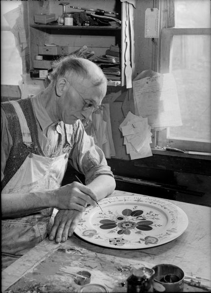 Per Lysne rosemaling a smorgasbord platter, Stoughton, ca. 1941. Photo by Arthur M. Vinje. Wisconsin Historical Society image ID 38105.