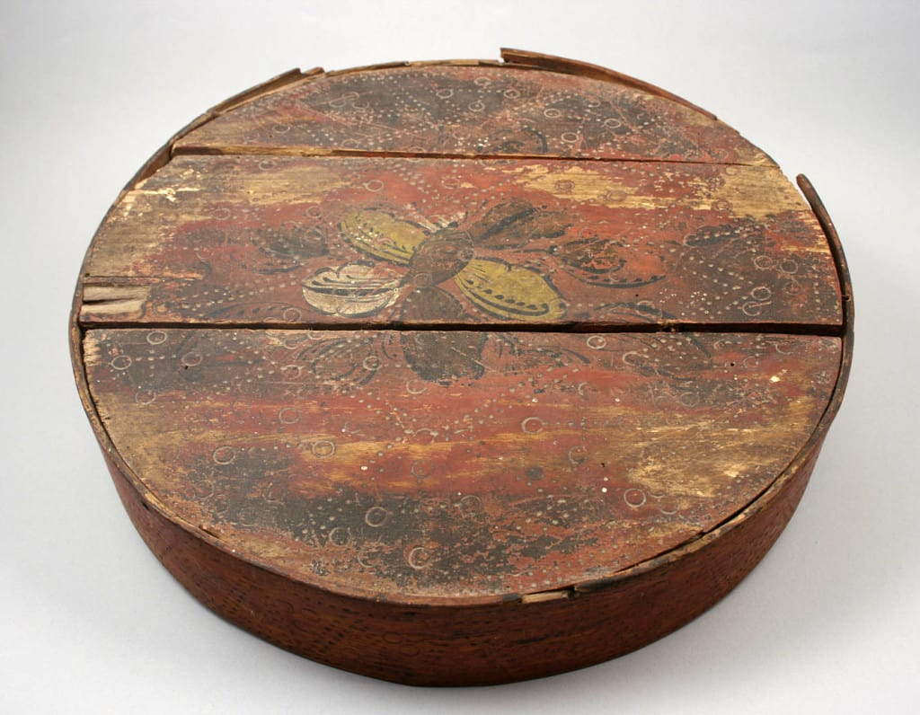 This bentwood box, made in Norway in the 19th century, is painted with simple green and yellow scrolls around the sides and a floral design in white, yellow and black on the lid. McFarland Historical Society.