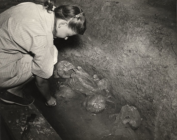 Anthropologist Charlotte Bakken works to uncover skeletons in a trench during the excavation of the Frost Woods Mounds in Monona. Photograph by Hal Roach, 1948. University of Wisconsin-Madison Archives.