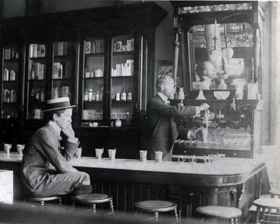 John Milton Granger sits on a caned stool at the marble-topped counter of Sykes Drug Store in Milwaukee, 1890s. Note the medicine bottles in the glass case next to the soda fountain. Milwaukee Public Library.