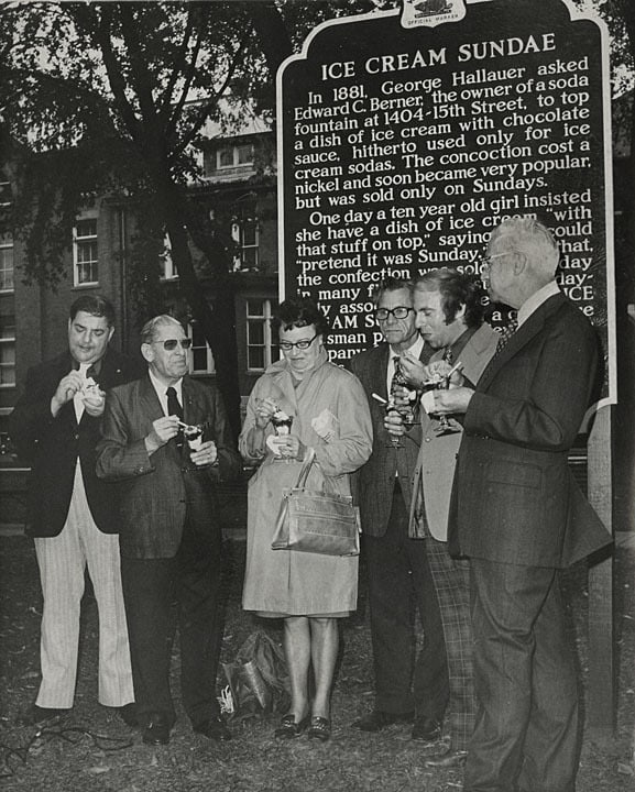 Joseph Schmitt, Seymour Althen, Henry Willert, Howard Messerman and Hilary Rath eating ice cream in front of Ice Cream Sundae historical marker, Two Rivers. Photo by Hubert R. Wentorf. Lester Public Library.