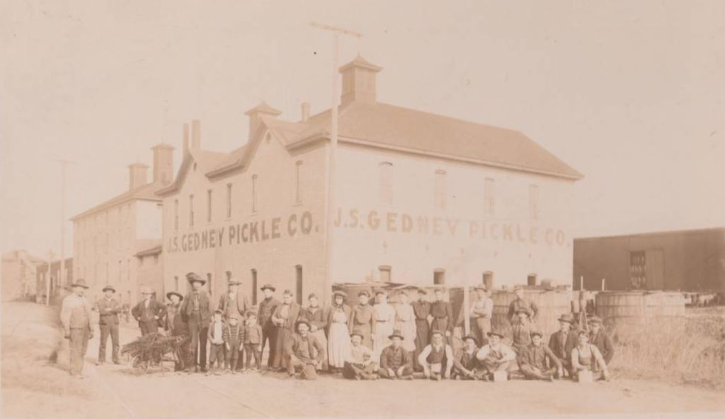 Exterior view of Onalaska Pickle and Canning Company with employees